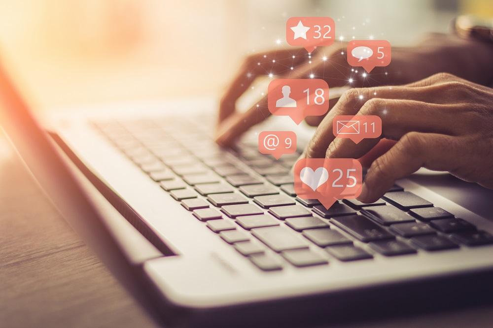 Une professionnelle utilise son ordinateur portable pour gérer ses réseaux sociaux