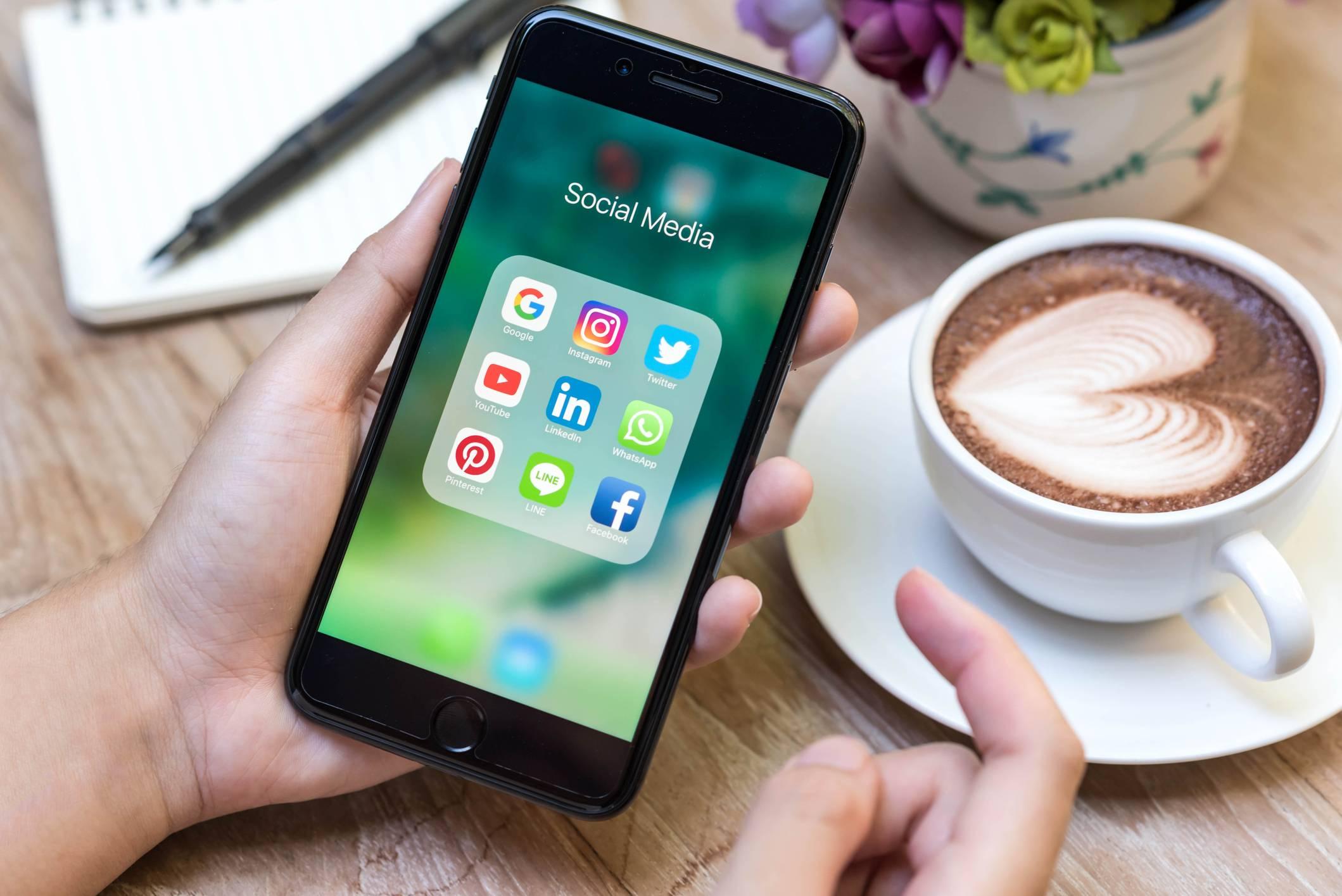 Une personne buvant son café et utilisant les réseaux sociaux