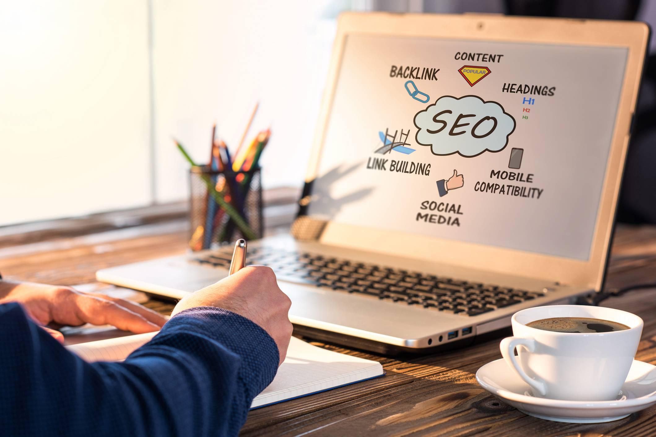 Une personne devant son ordinateur portable mettant en place du référencement SEO