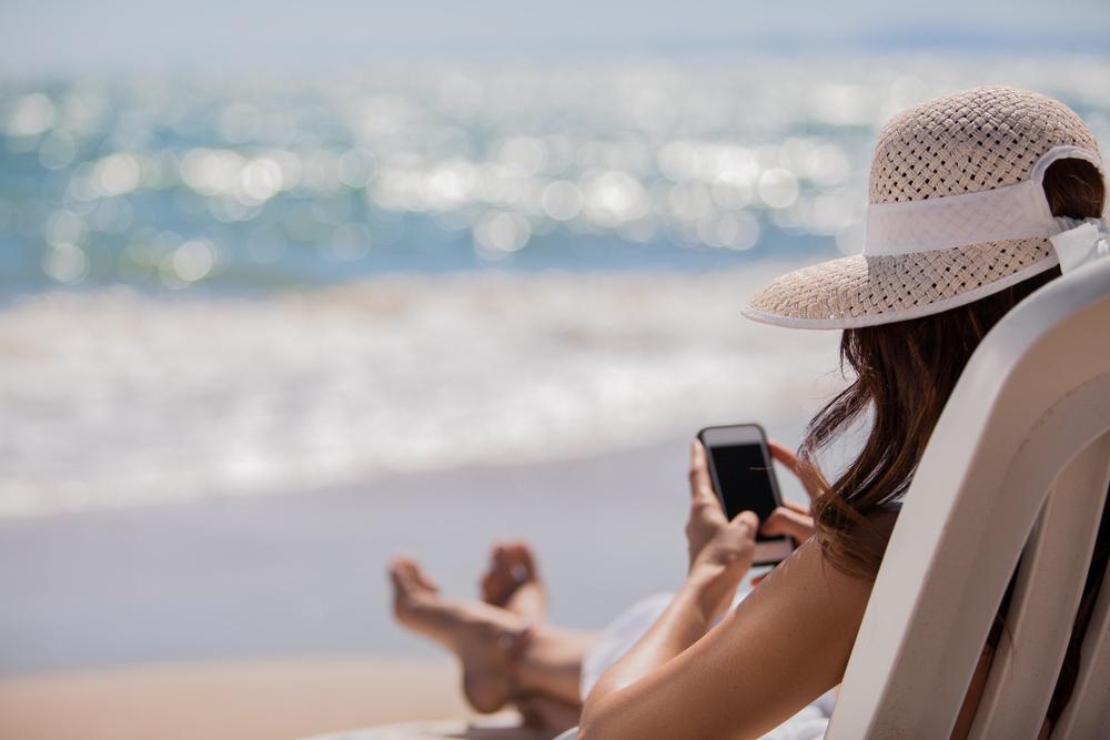 Jeune femme sur un transat à la plage consultant son téléphone mobile.